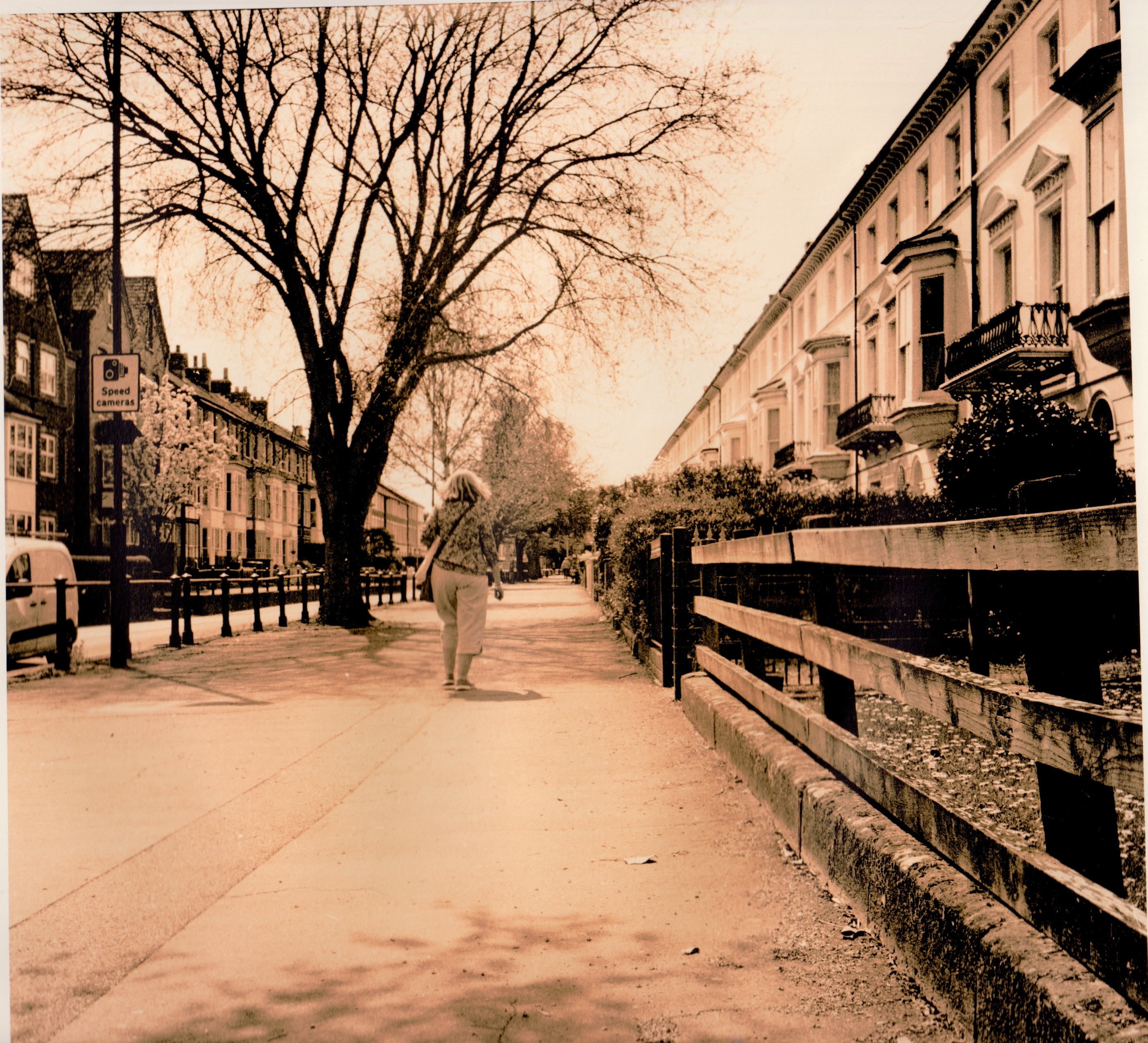 A lith print of a woman walking down a pavement with buildings either side.