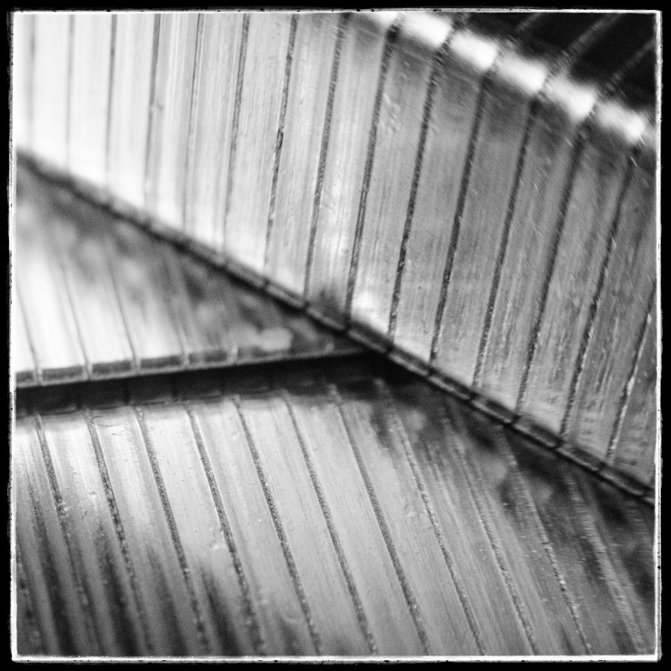 An abstract, black and white, macro photograph of some strips of staples.